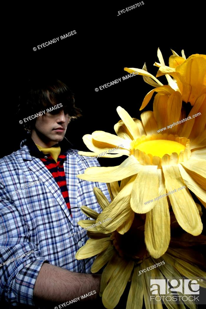 Stock Photo: Young man with paper sunflowers.