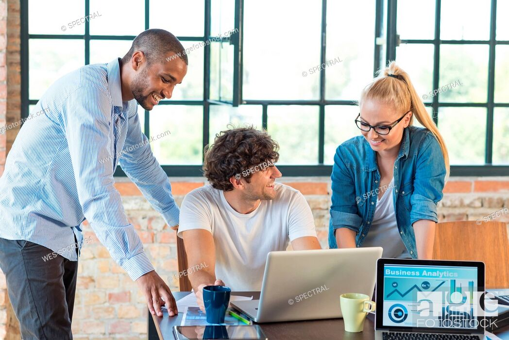 Stock Photo: Young professionals working together in start up company, developing a business plan.