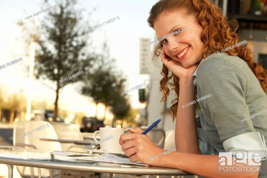 Stock Photo: Young woman writing at outdoor cafe portrait.