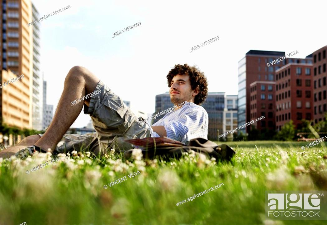Stock Photo: Germany, Berlin, Man relaxing on lawn, in background high rise buildings.