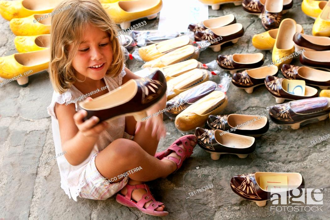 Stock Photo: Girl sitting on the floor picking up a shoe.
