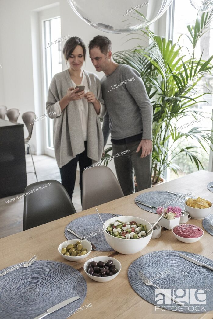 Stock Photo: Couple taking a picture of their vegetarian meal to share on social media.