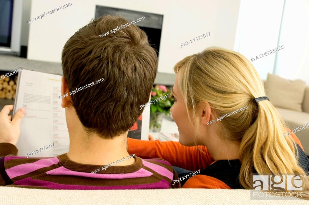 Stock Photo: Rear view of a young couple reading a magazine.
