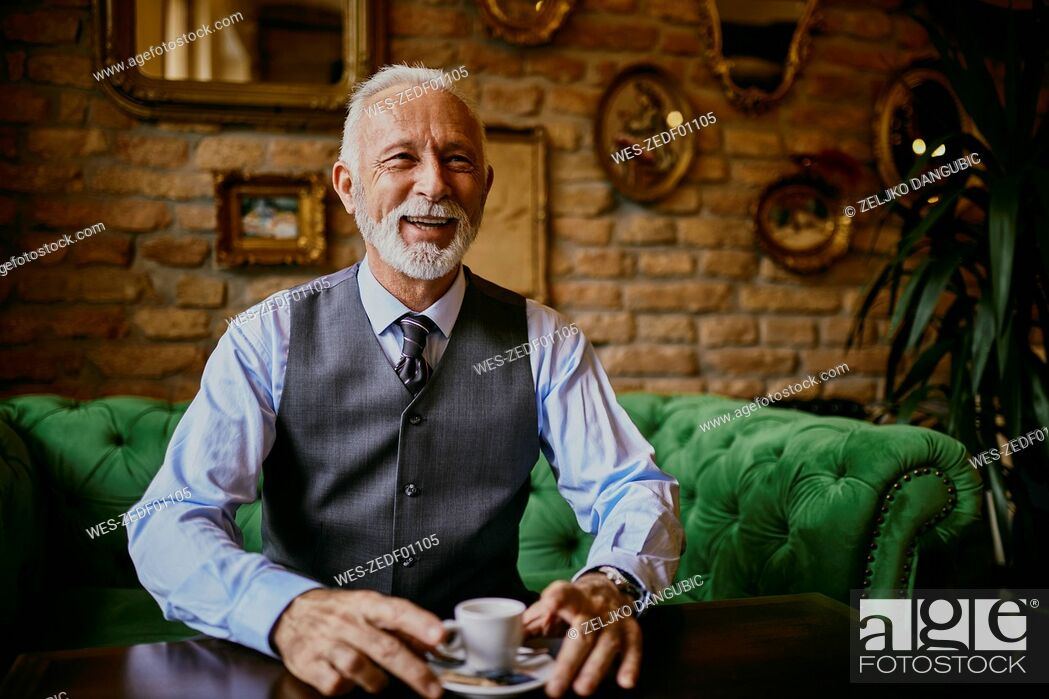Stock Photo: Portrait of elegant senior man sitting on couch in a cafe smiling.