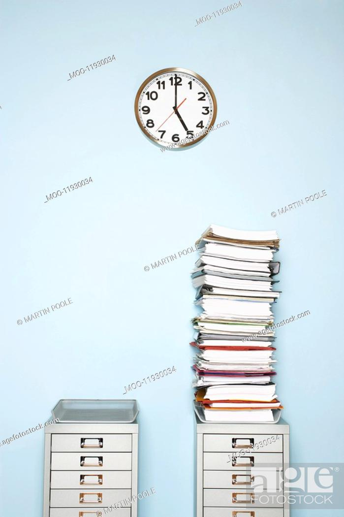 Stock Photo: Office wall with clock stack of paperwork in outbox on file cabinet.