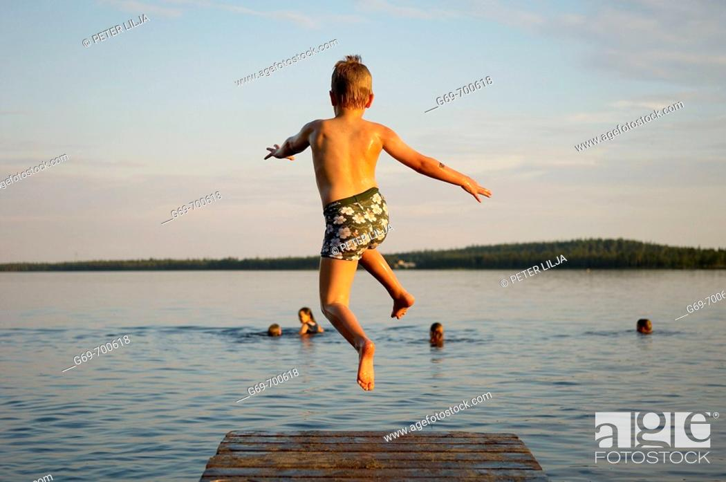 Stock Photo: 7 year old boy and jumping from a jetty, Norrbotten, Sweden (July 2005).
