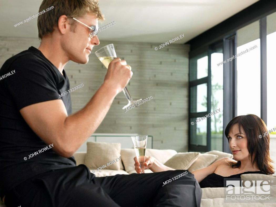 Stock Photo: Young man and woman drinking champagne in living room.