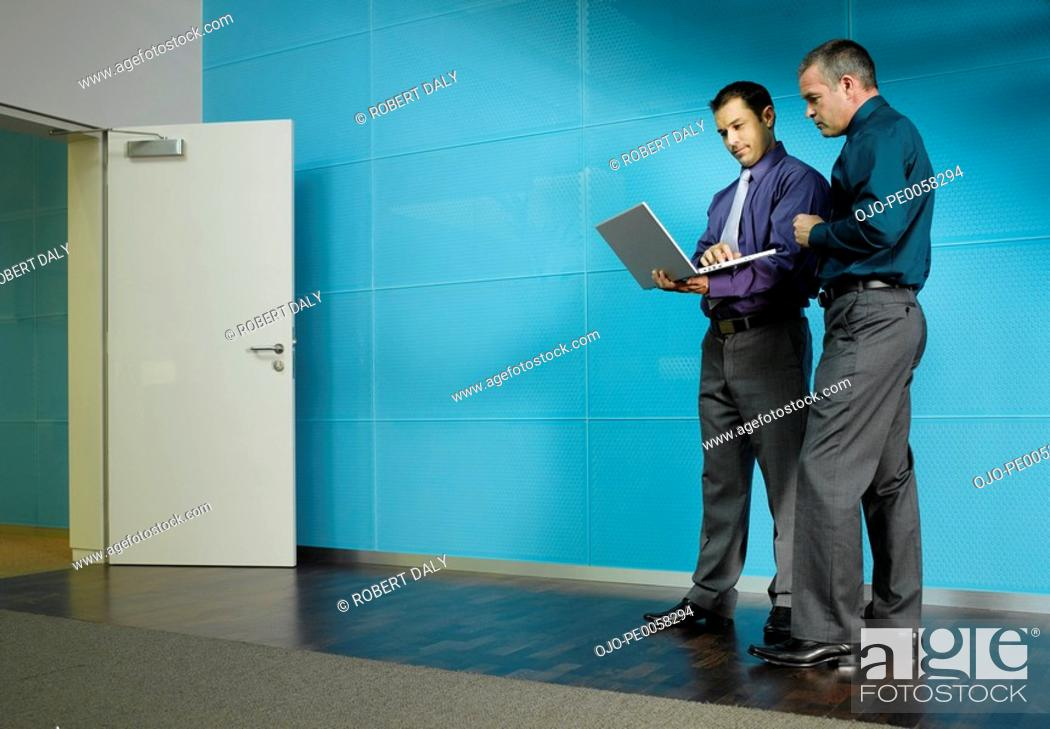 Stock Photo: Two businessmen with a laptop in blue office.