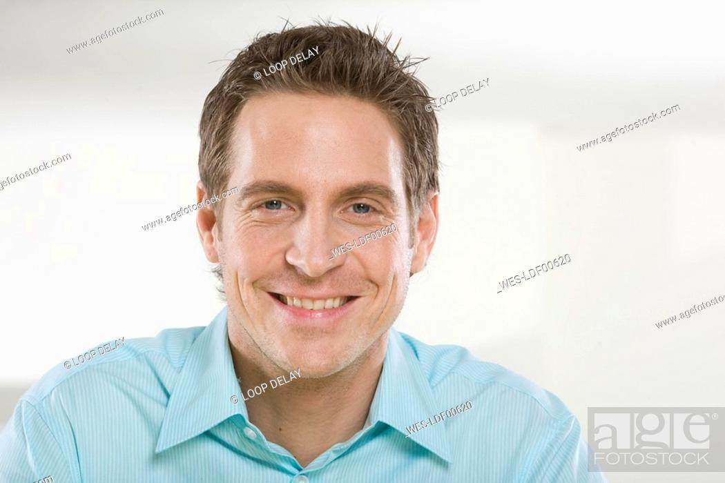 Stock Photo: Young man smiling, portrait, close-up.