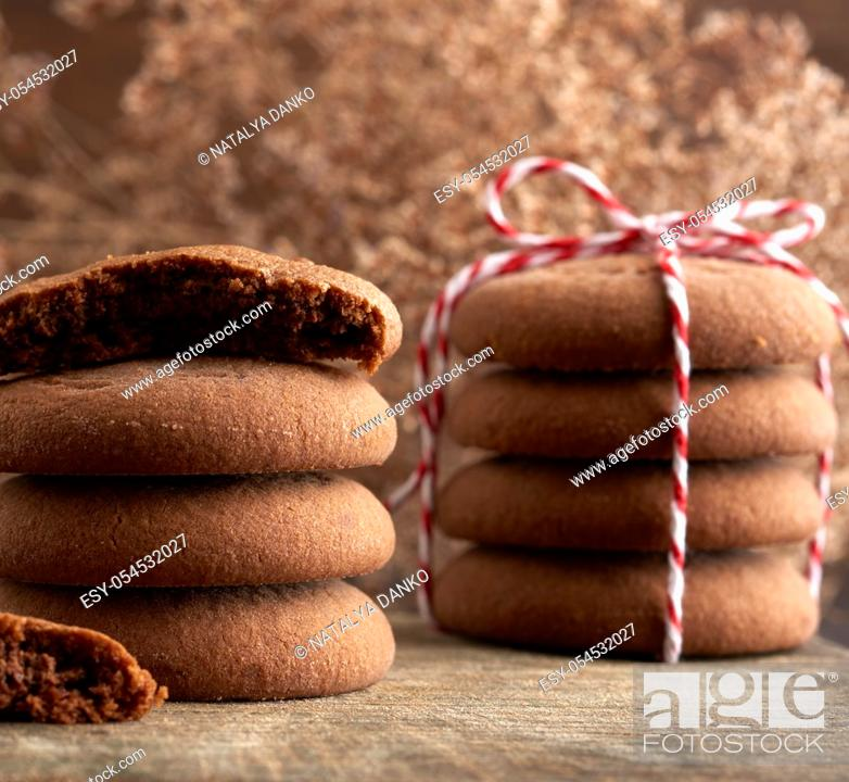 Stock Photo: stack of round chocolate chip cookies tied with a rope on a brown board, delicious dessert.