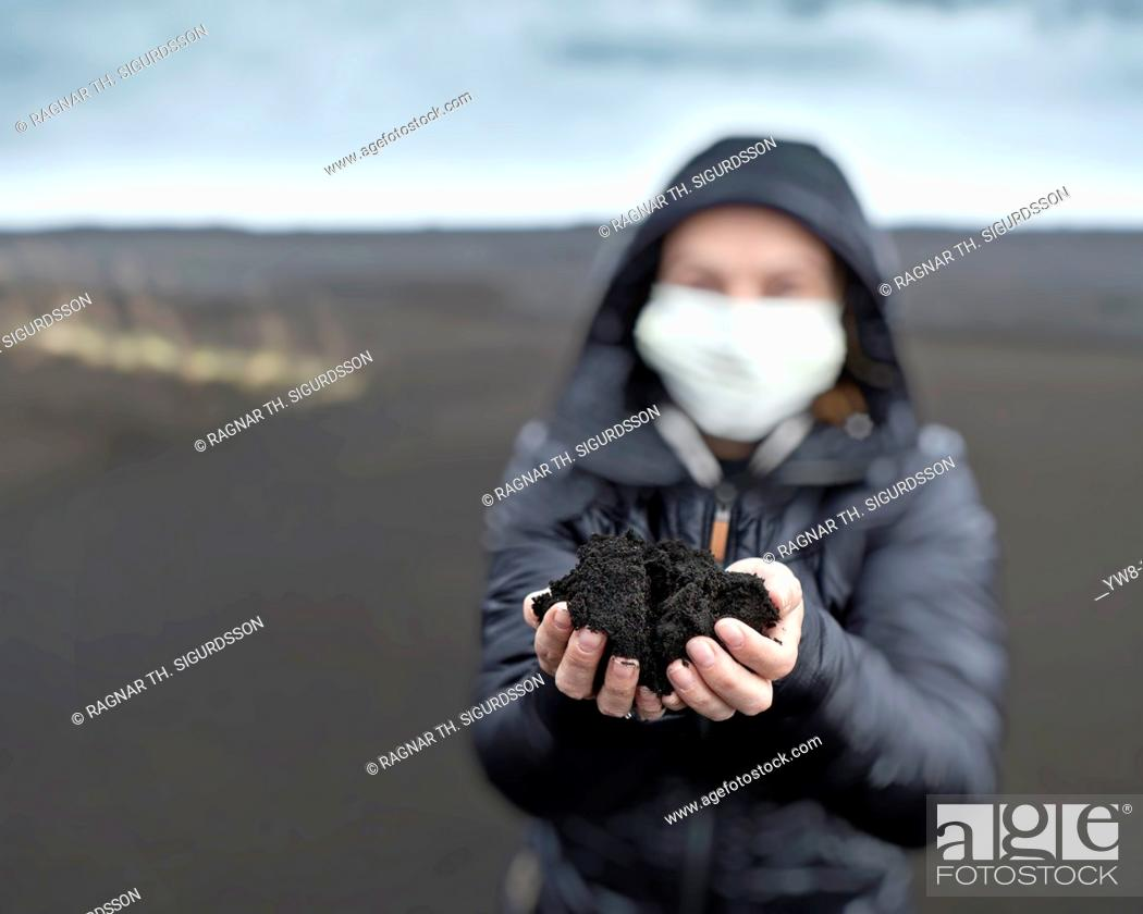 Stock Photo: Woman holding new ash from recent Grimsvotn volcanic eruption, Iceland  Skeidararsandur outwash plains covered with ashfall  Eruption began on May 21, 2011.