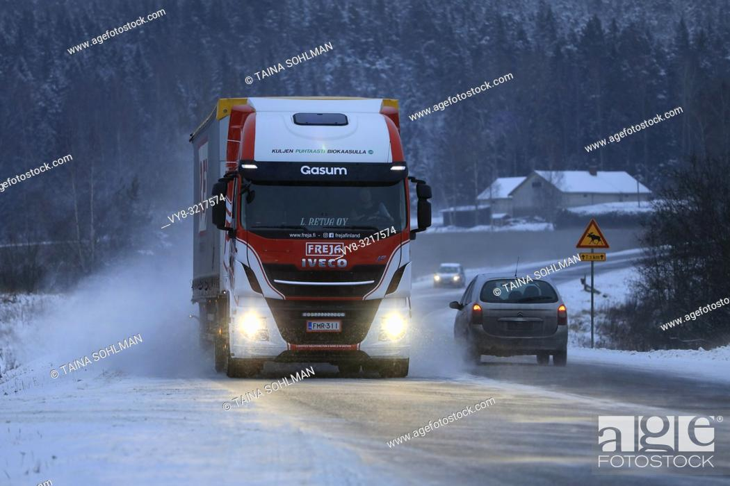 Stock Photo: Salo, Finland - December 22, 2018: Biogas fueled Iveco Stralis NP truck L. Retva Oy pulls FREJA trailer along snowy highway in winter evening traffic.