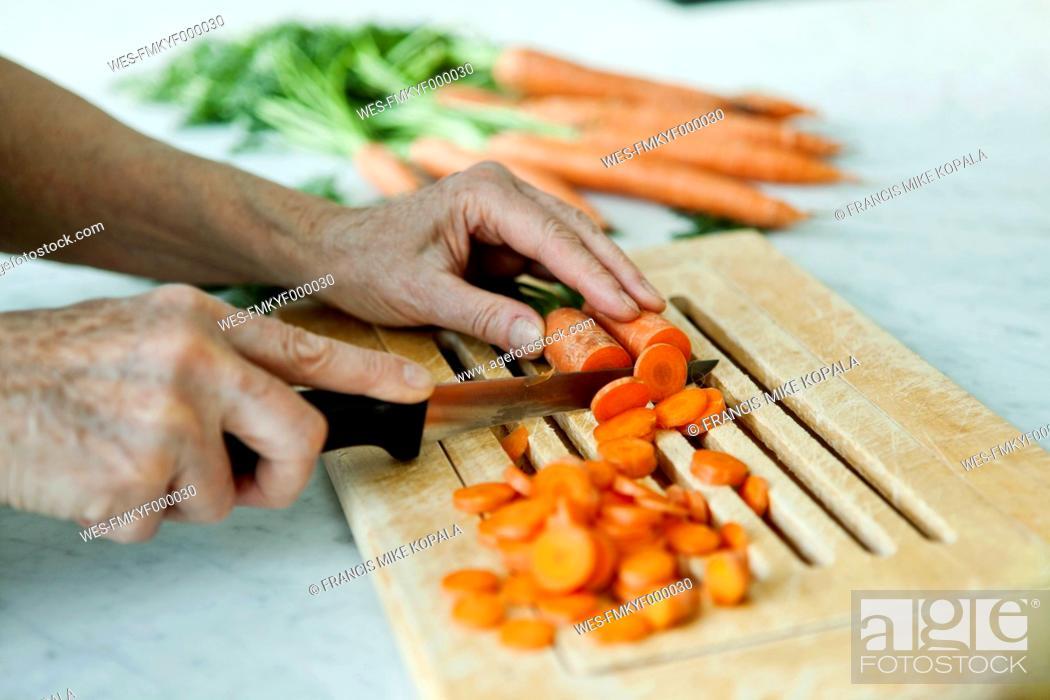 Stock Photo: Germany, Berlin, Senior man cutting carrots.