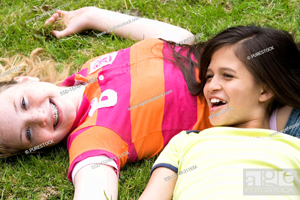 Stock Photo: High angle view of two girls lying on the grass and smiling.