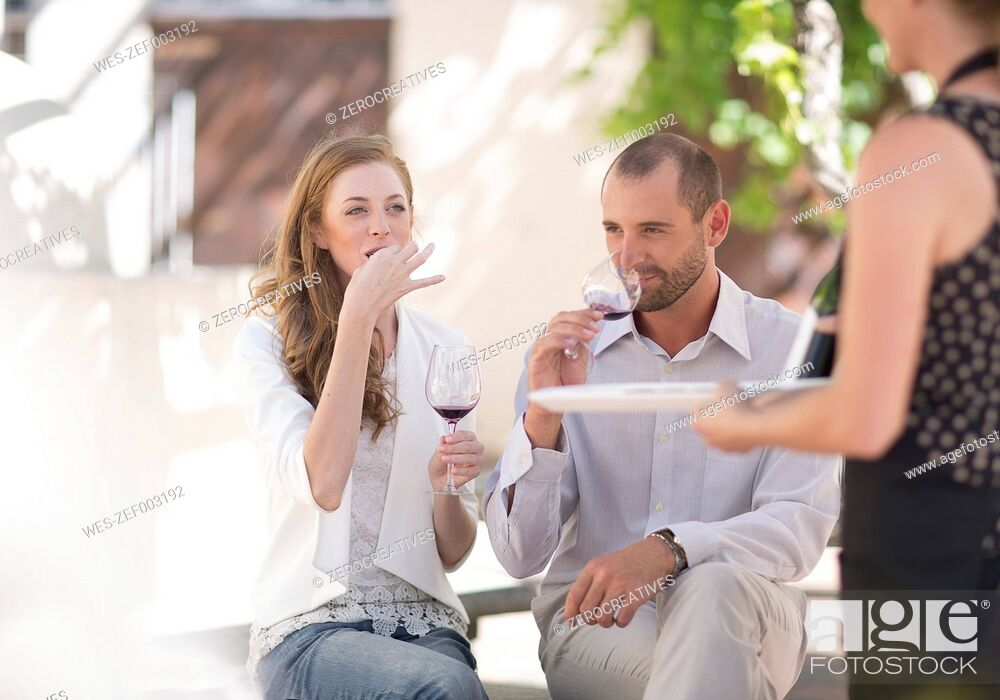 Stock Photo: Waitress with tray and couple sitting outdoors tasting red wine.
