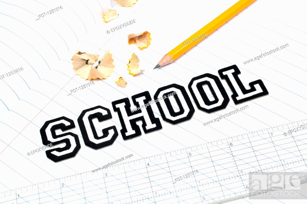 Stock Photo: Varsity font stickers spelling out School atop a lined paper notebook with ruler and pencil.