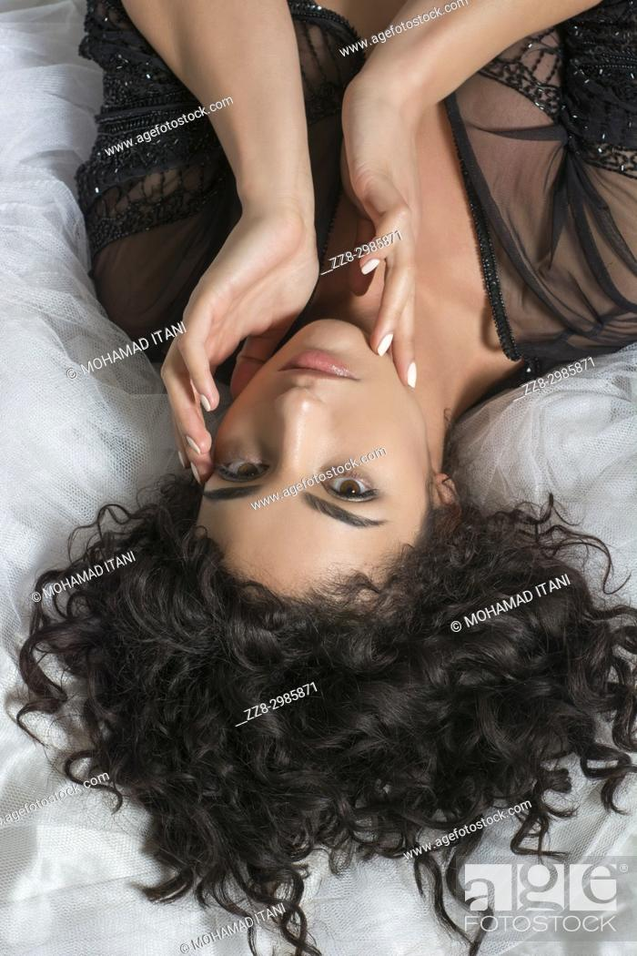 Stock Photo: Beautiful young woman wearing sheer robe laying down in bed hand touching face.