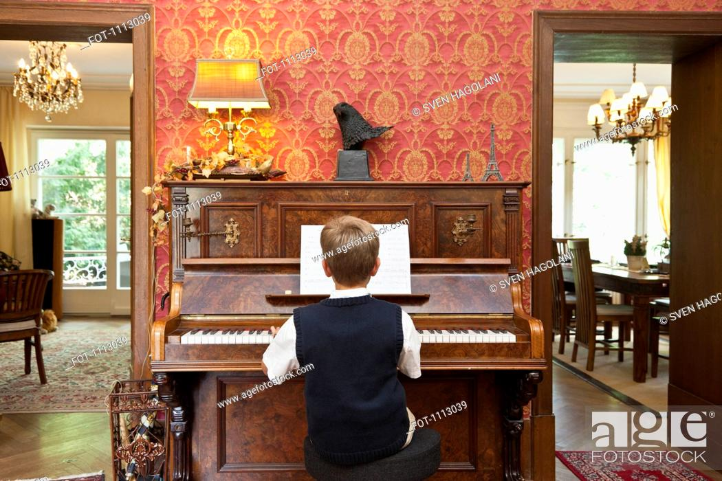 Stock Photo: A boy practicing on an old-fashioned upright piano.