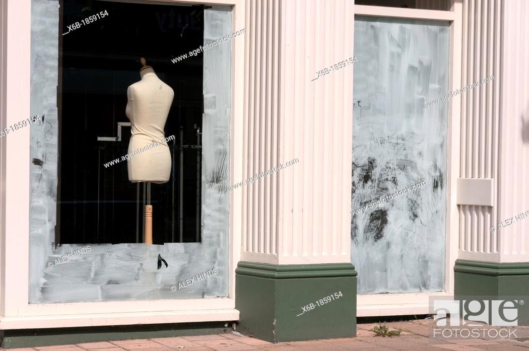 Stock Photo: Fashion mannequin seen through whitewashed windows of an out of business closed shop.