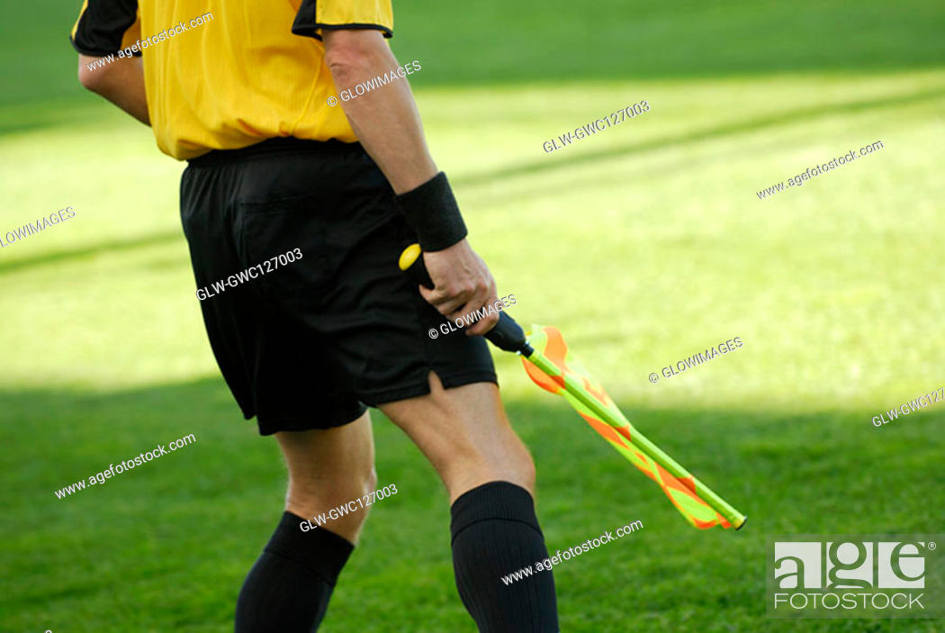 Stock Photo: Mid section view of a referee holding a flag.