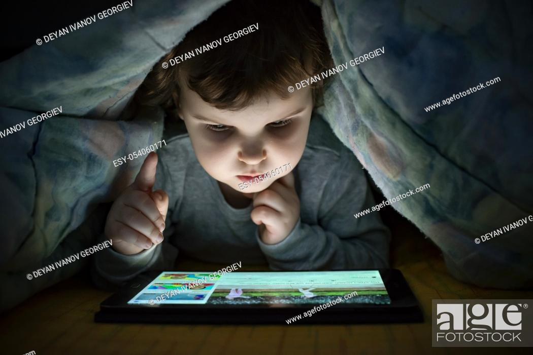 Stock Photo: Little girl watching her tablet in the bed. Illuminated child face from device screen. Child dressed with pajamas under the covers hold a tablet.