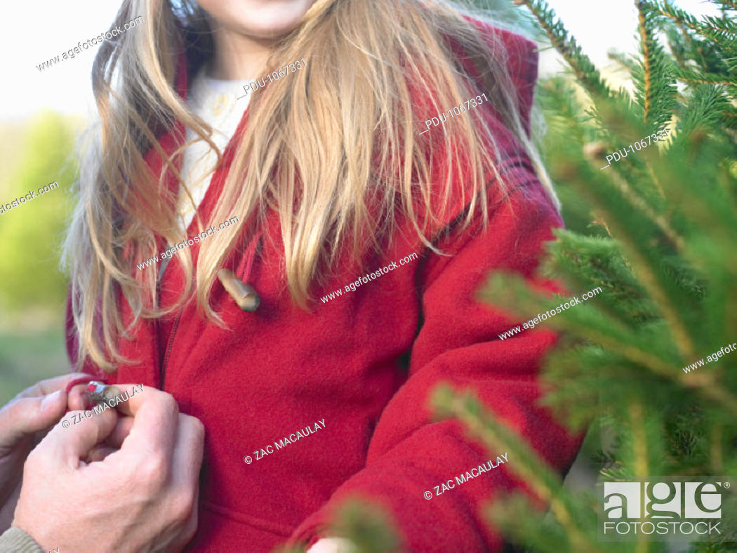 Stock Photo: Father buttoning  daughter's (5-7) coat, mid section, close-up.