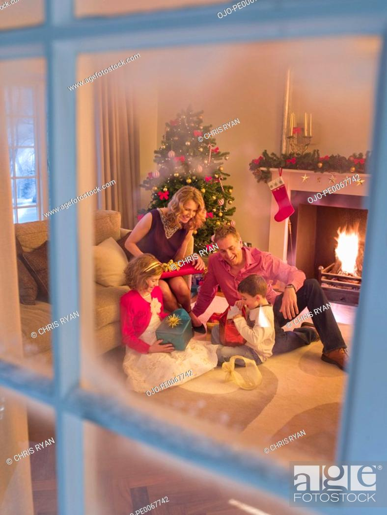 Stock Photo: Family opening Christmas gifts in living room.