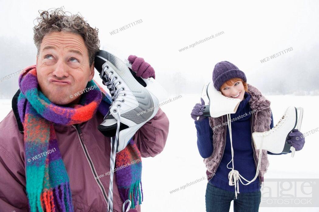 Stock Photo: Italy, South Tyrol, Seiseralm, Couple on frozen lake, carrying ice skates.