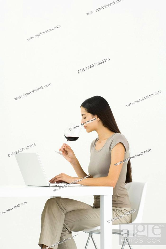 Stock Photo: Woman using laptop at table, holding glass of wine.