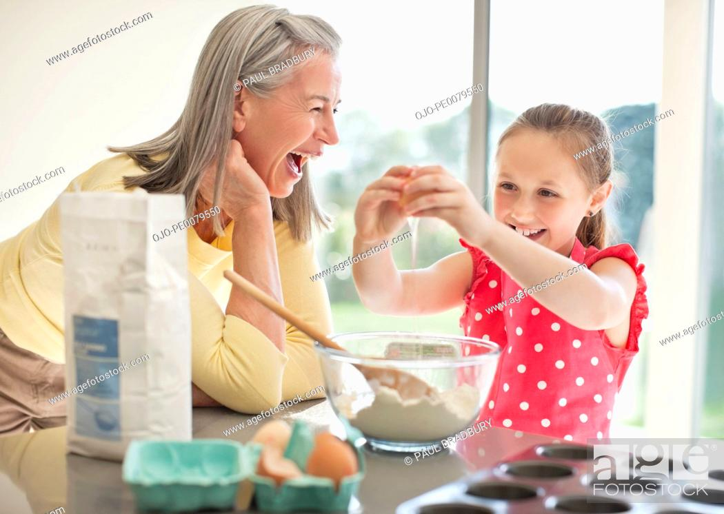 Stock Photo: Grandmother and granddaughter baking cupcakes.