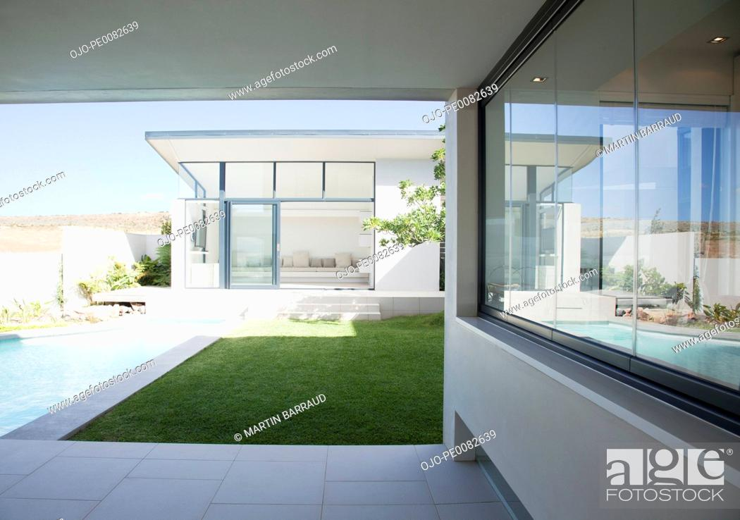 Stock Photo: Patio and pool adjoining modern house.