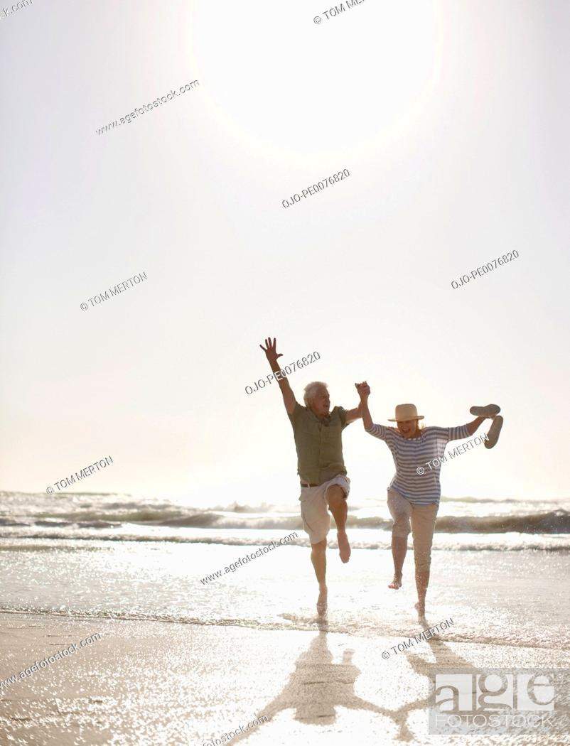 Stock Photo: Senior couple jumping on beach.