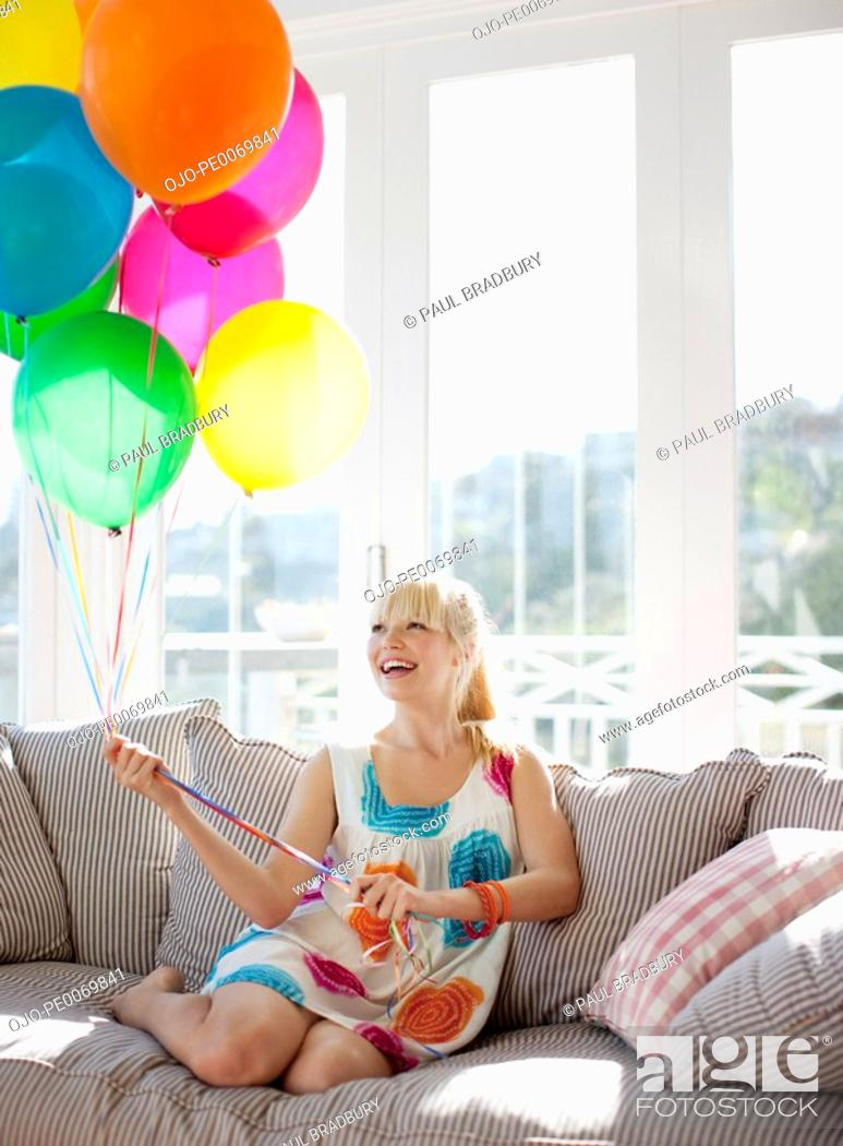 Stock Photo: Woman holding balloons on sofa in living room.