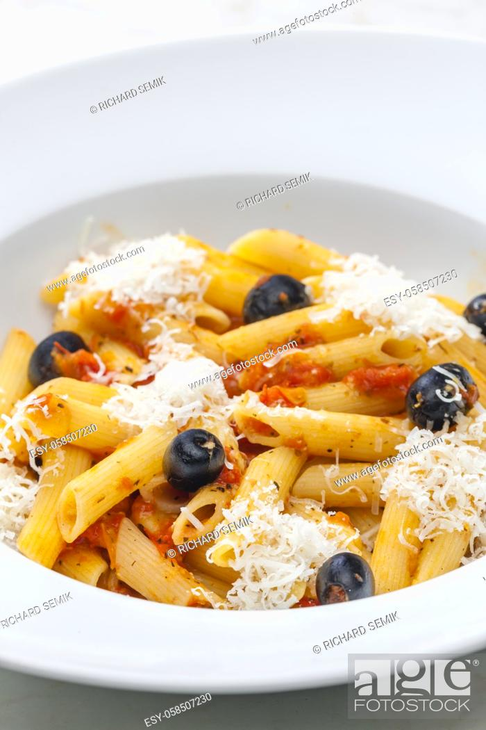 Stock Photo: penne pasta with tomato sauce, black olives and parmesan cheese.