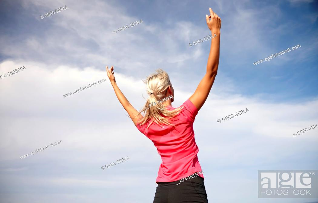 Stock Photo: Woman with arms raised in the air.