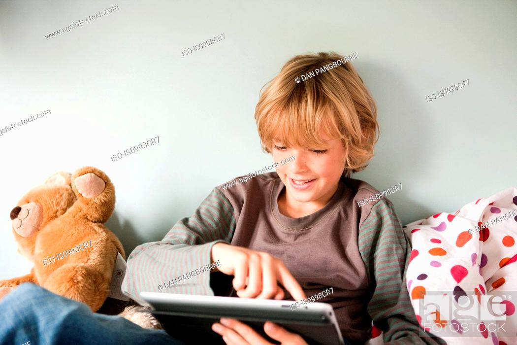 Stock Photo: Young boy using a digital tablet while sitting on his bed.