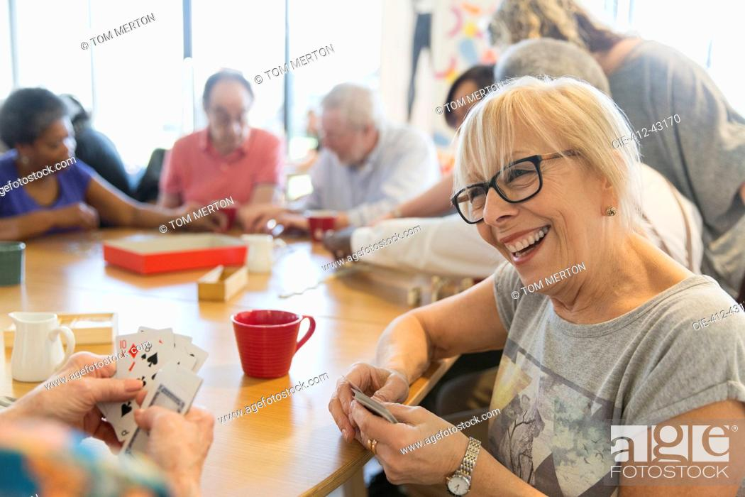 Stock Photo: Happy senior woman playing cards with friend at table in community center.