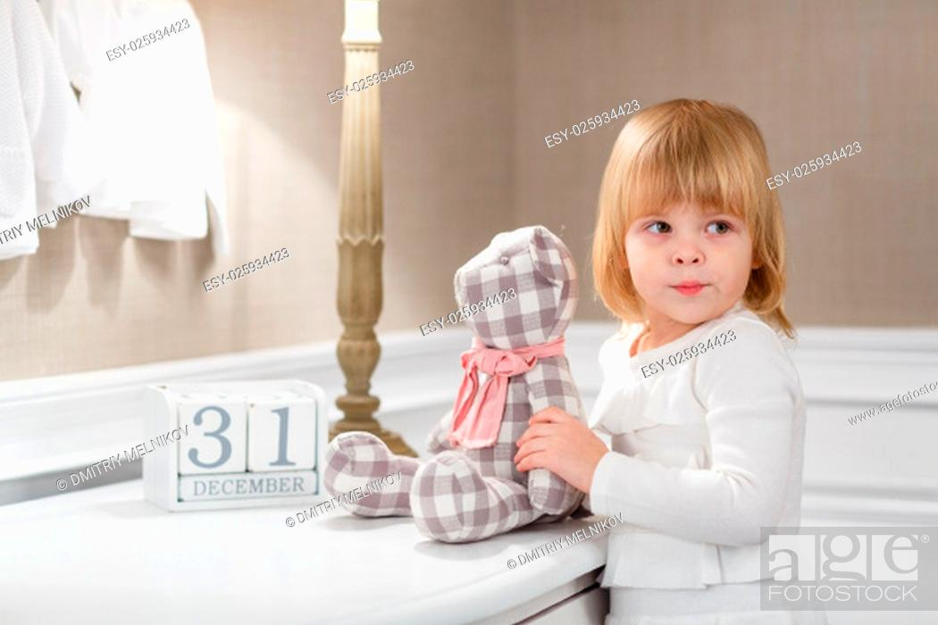 Stock Photo: Happy sweet little girl with date 31 december stands in the room . Eve of New Year.
