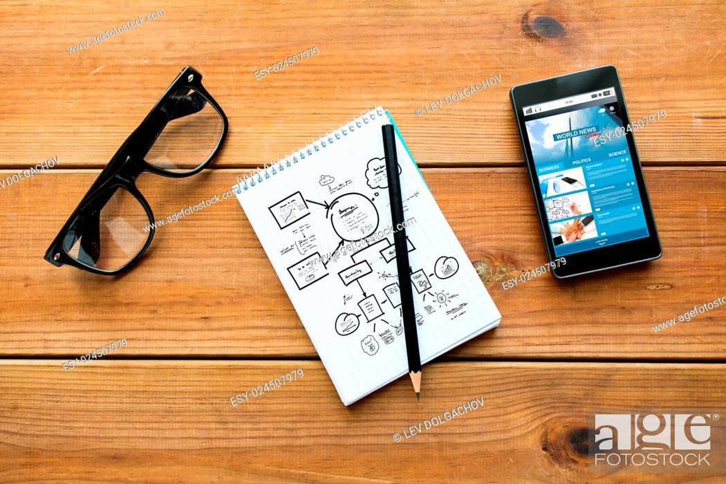 Stock Photo: mass media, business, planning and technology concept - close up of scheme drawing in notepad with pencil, with world news on smartphone and eyeglasses on.