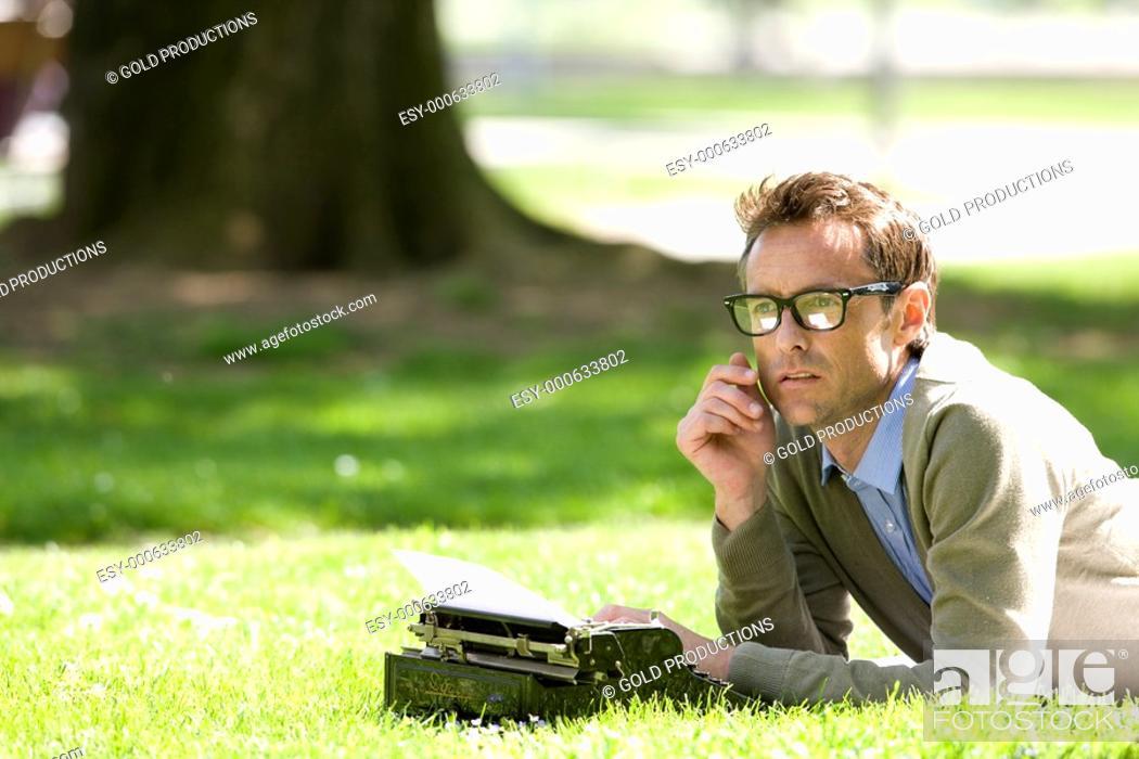 Stock Photo: man writing on a vintage typewriter.