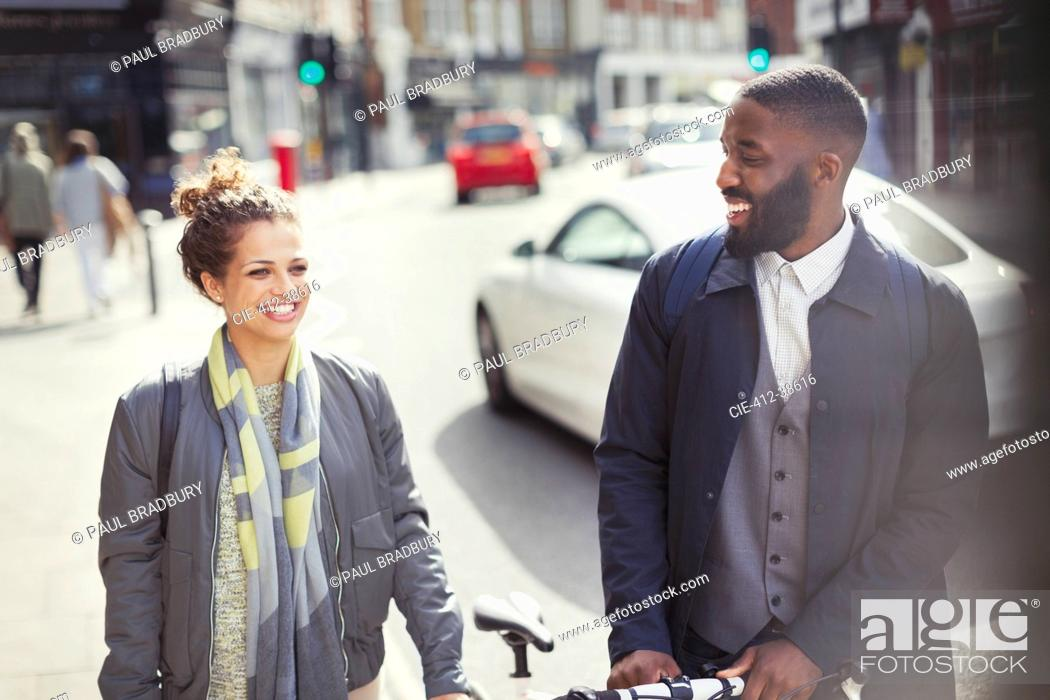 Stock Photo: Smiling couple commuting with bicycle on sunny urban street.