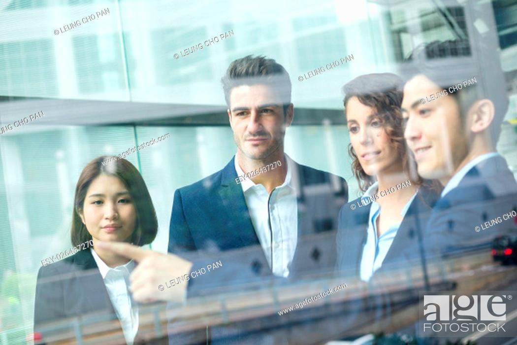 Stock Photo: Group of business people discuss something inside office.