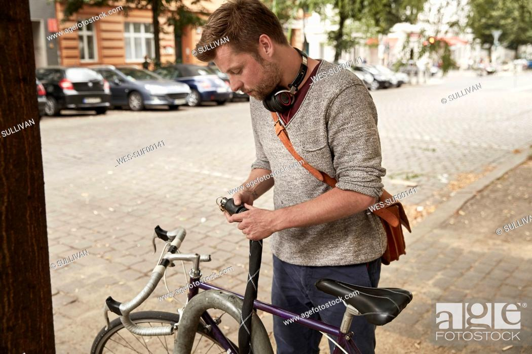 Photo de stock: Man locking bicycle in the city.