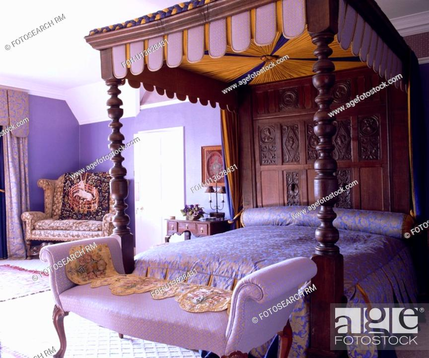 Stock Photo Small Chaiselongue Below Antique Tudor Carved Wood Fourposter Bed In Purple Country Bedroom