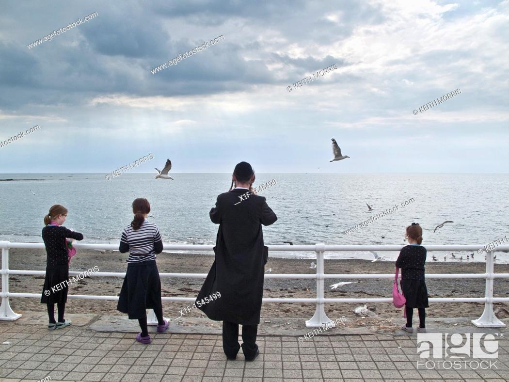 Stock Photo: Orthodox hasidic jewish families on summer holiday in Aberystwyth Ceredigion Wales UK.