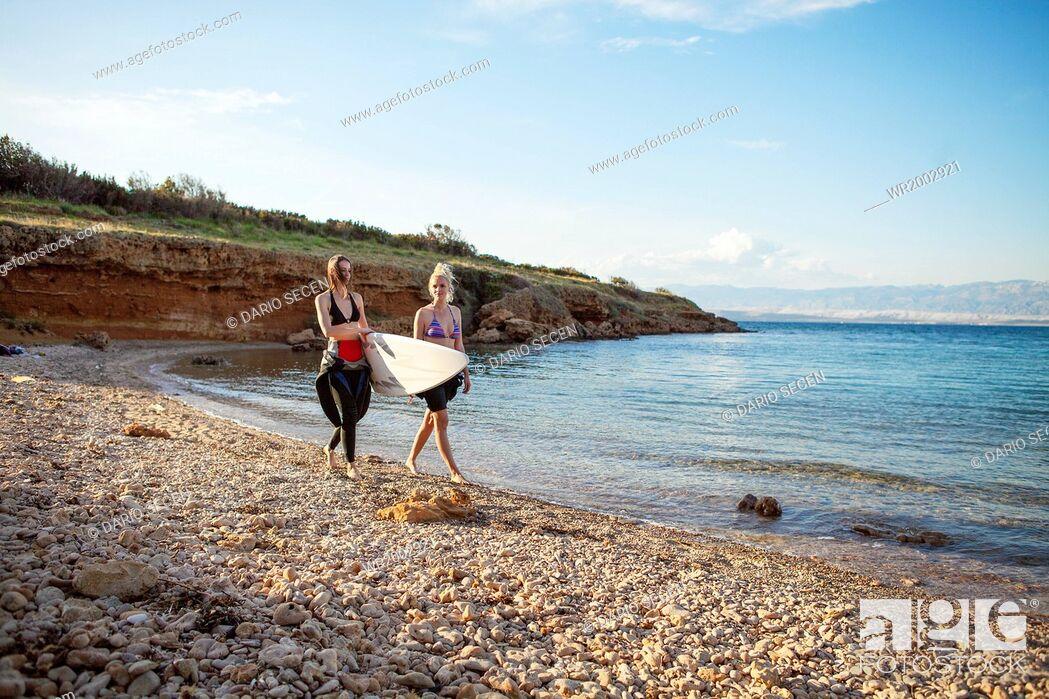 Stock Photo: Female surfers on beach.