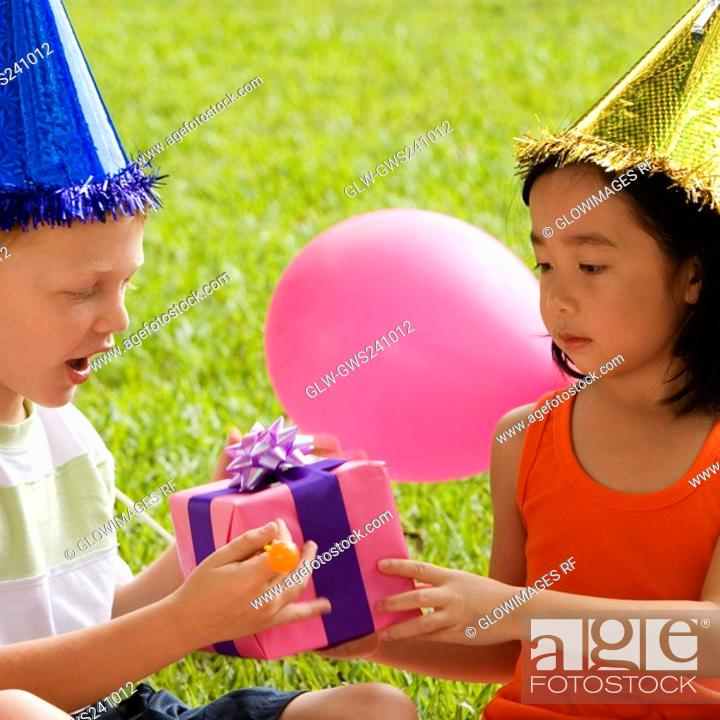 Stock Photo: Close-up of a boy giving a birthday present to a girl.