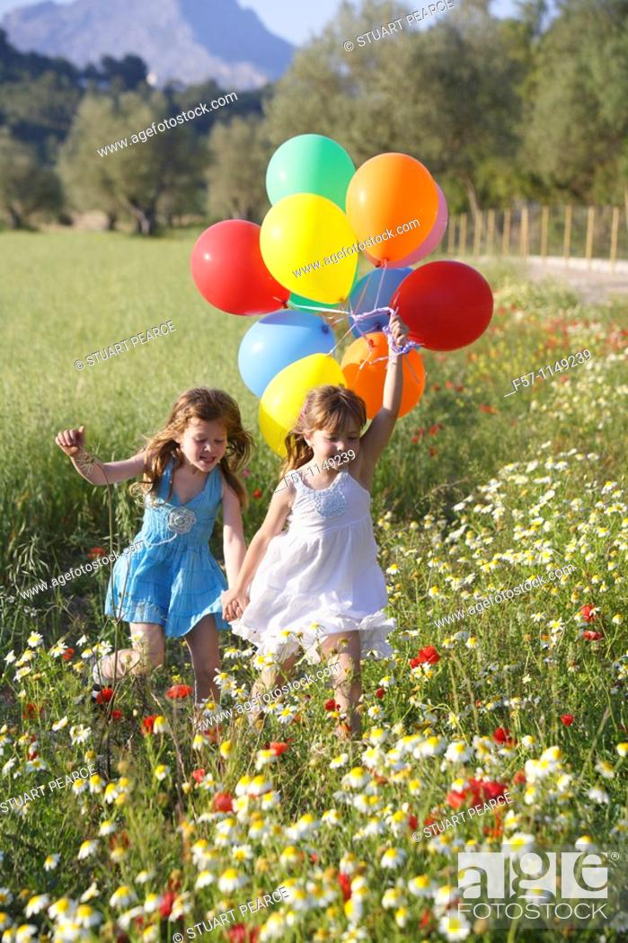 Stock Photo: Girls in meadow with balloons.