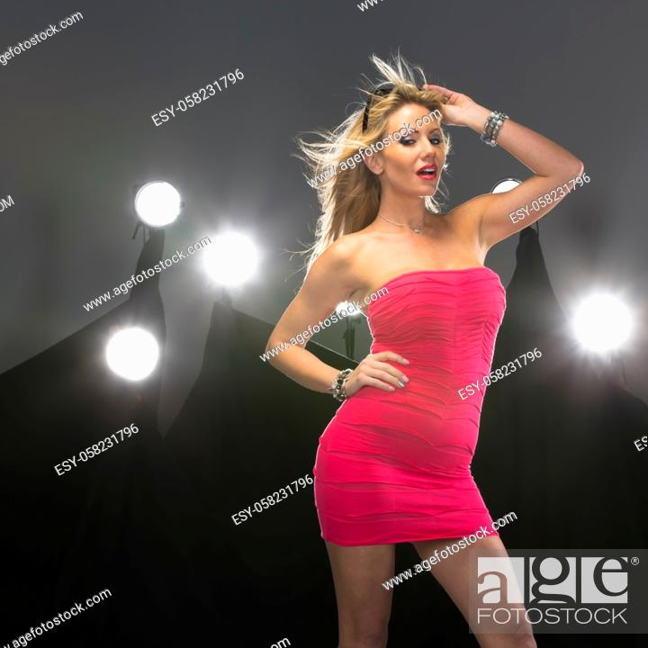Stock Photo: An attractive blonde lingerie model poses in a studio environment with lights in the background.A blonde attractive model poses in a studio environment with.