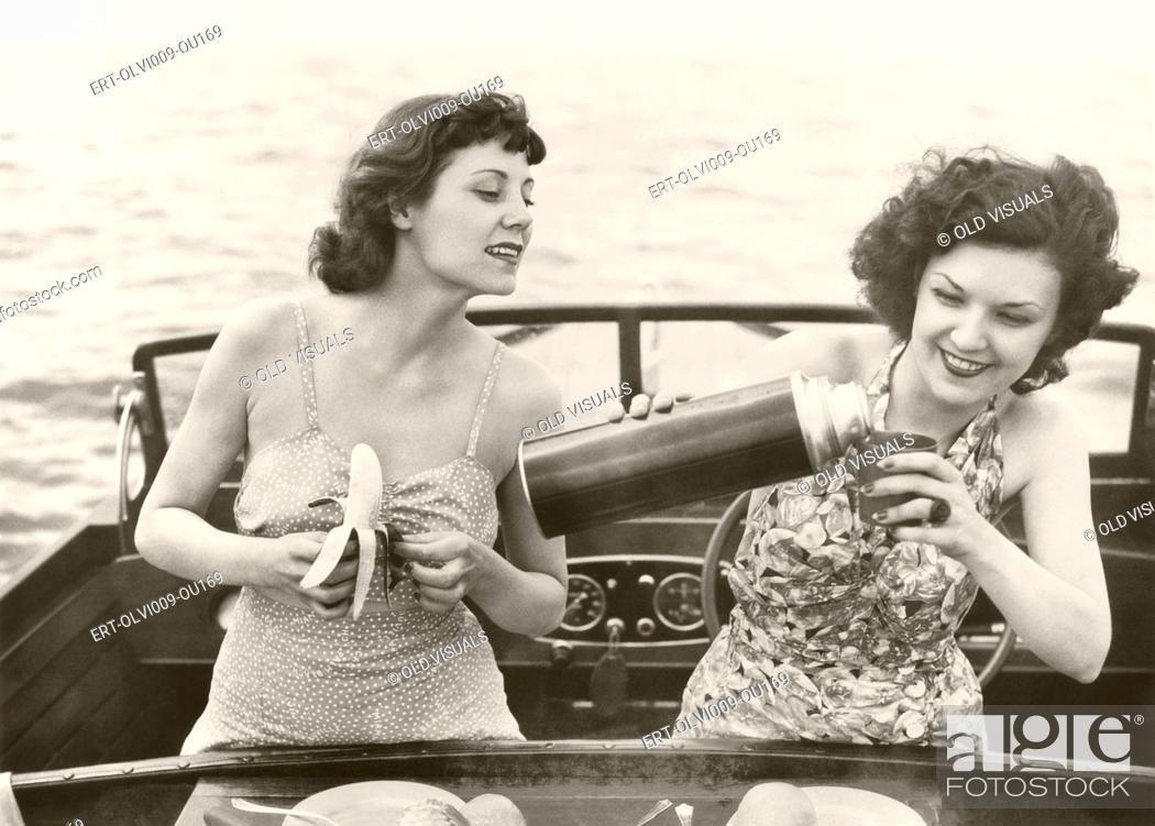 Stock Photo: Two women having a snack on motorboat.